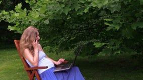 Blondynki dziewczyny rozmowy telefonu ciężarna przerwa od laptopu gawędzenia parka zbiory