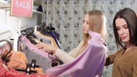 Blondynki i brunetki dyskutować odziewa w sklepie Dwa pięknej kobiety z odzieżowymi wieszakami wokoło przyglądających strojów zbiory