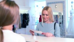 Blondynki kobieta dostaje ewidencyjnych prześcieradła od konsultanta przy biurkiem splendor sukni butik zdjęcie wideo