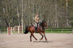 Blondynki kobieta jedzie podpalanego konia Zdjęcia Royalty Free