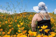 Blondynki kobieta jest ubranym czapeczka kapeluszu s?omianych spojrzenia za polu makowi wildflowers podczas superbloom obraz royalty free