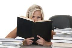 Blondynki kobieta ono przygląda się nad książką Obrazy Stock