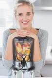 Blondynki kobieta opiera na jej juicer owocowy pełno i ono uśmiecha się przy Obrazy Royalty Free