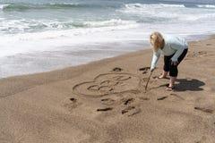 Blondynki kobieta pisze Bae argot dla Anyone Innego Przed, reprezentuje romantycznego związek w piasku na plaży zdjęcie royalty free