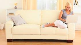 Blondynki kobieta relaksuje na kanapie z notatnikiem zbiory wideo