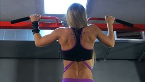 Blondynki kobieta robi ciągnieniu podnosi przy gym Zdjęcie Stock