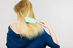 Blondynki kobieta szczotkuje włosy tylnego widok Zdjęcie Royalty Free