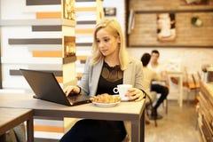 Blondynki kobieta używa laptop w internet kawiarni Fotografia Royalty Free