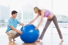 Blondynki kobieta w ciąży ćwiczy z trenerem i piłką Obrazy Royalty Free
