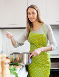 Blondynki kobieta w fartuch kulinarnej polewce obraz stock