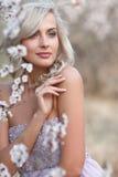 Blondynki kobieta w kwitnącym ogródzie fotografia royalty free