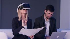 Blondynki kobieta w VR słuchawki mienia budowy planach podczas gdy jej męski partner pisać na maszynie na laptopie Fotografia Royalty Free