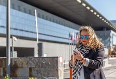 Blondynki kobieta z czarnymi szkłami i przypadkowymi ubraniami słucha muzyka z jej hełmofonami i sprawdza jej telefon komórkowego zdjęcie stock
