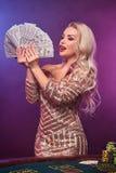 Blondynki kobieta z doskonalić fryzurą jaskrawym makijażem i pozuje z fan sto dolarowych rachunków w jej rękach kasyno zdjęcia royalty free