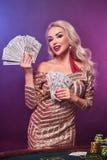 Blondynki kobieta z doskonalić fryzurą jaskrawym makijażem i pozuje z fan sto dolarowych rachunków w jej rękach kasyno zdjęcie royalty free