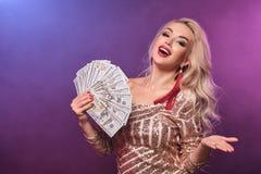 Blondynki kobieta z doskonalić fryzurą jaskrawym makijażem i pozuje z fan sto dolarowych rachunków w jej rękach kasyno zdjęcie stock