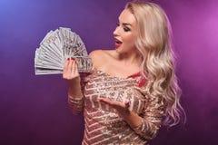 Blondynki kobieta z doskonalić fryzurą jaskrawym makijażem i pozuje z fan sto dolarowych rachunków w jej rękach kasyno fotografia royalty free