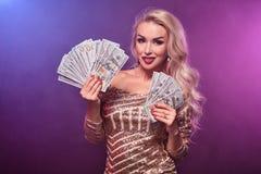 Blondynki kobieta z doskonalić fryzurą jaskrawym makijażem i pozuje z fan sto dolarowych rachunków w jej rękach kasyno zdjęcia stock
