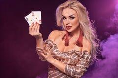 Blondynki kobieta z doskonalić fryzurą jaskrawym makijażem i pozuje z kartami do gry w jej rękach Kasyno, grzebak zdjęcia royalty free