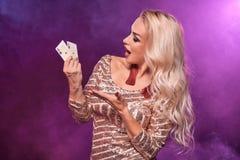 Blondynki kobieta z doskonalić fryzurą jaskrawym makijażem i pozuje z kartami do gry w jej rękach Kasyno, grzebak fotografia royalty free