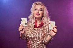 Blondynki kobieta z doskonalić fryzurą jaskrawym makijażem i pozuje z kartami do gry w jej rękach Kasyno, grzebak obraz stock