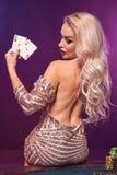 Blondynki kobieta z doskonalić fryzurą jaskrawym makijażem i pozuje z kartami do gry w jej rękach Kasyno, grzebak zdjęcia stock