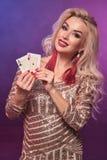Blondynki kobieta z doskonalić fryzurą jaskrawym makijażem i pozuje z kartami do gry w jej rękach Kasyno, grzebak obraz royalty free