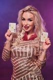 Blondynki kobieta z doskonalić fryzurą jaskrawym makijażem i pozuje z kartami do gry w jej rękach Kasyno, grzebak obrazy royalty free