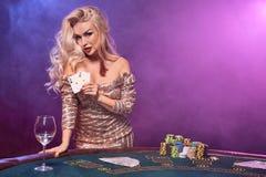 Blondynki kobieta z doskonalić fryzurą jaskrawym makijażem i pozuje z kartami do gry w jej rękach Kasyno, grzebak zdjęcie stock