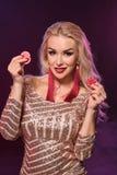 Blondynki kobieta z doskonalić fryzurą jaskrawym makijażem i pozuje z uprawiać hazard układy scalonych w jej rękach Kasyno, grzeb fotografia stock