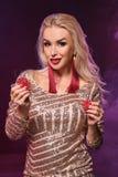 Blondynki kobieta z doskonalić fryzurą jaskrawym makijażem i pozuje z uprawiać hazard układy scalonych w jej rękach Kasyno, grzeb obraz stock