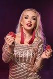 Blondynki kobieta z doskonalić fryzurą jaskrawym makijażem i pozuje z uprawiać hazard układy scalonych w jej rękach Kasyno, grzeb obrazy stock