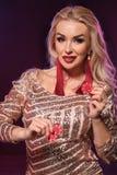 Blondynki kobieta z doskonalić fryzurą jaskrawym makijażem i pozuje z uprawiać hazard układy scalonych w jej rękach Kasyno, grzeb obraz royalty free