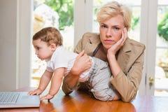 Blondynki kobieta z jego synem używa laptop Obraz Stock