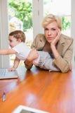 Blondynki kobieta z jego synem używa laptop Fotografia Stock