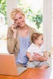 Blondynki kobieta z jego synem używa telefon i laptop Fotografia Stock