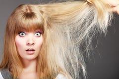 Blondynki kobieta z jej uszkadzającym suchym włosy Zdjęcia Royalty Free