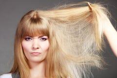 Blondynki kobieta z jej uszkadzającym suchym włosy Zdjęcie Royalty Free