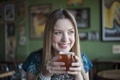 Blondynki kobieta z Pięknymi niebieskimi oczami Pije czara piwo Obraz Stock