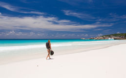 Blondynki kobieta z plecakiem i kapeluszem, spacery wzdłuż plaży Fotografia Royalty Free