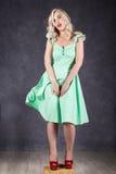 Blondynki kobieta z włosy w wiatrze seksowna dziewczyna z latającym włosy pozuje w zieleni czerwieni i sukni butach Obrazy Royalty Free