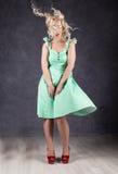 Blondynki kobieta z włosy w wiatrze seksowna dziewczyna z latającym włosy pozuje w zieleni czerwieni i sukni butach Zdjęcie Royalty Free
