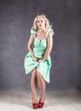 Blondynki kobieta z włosy w wiatrze seksowna dziewczyna z latającym włosy pozuje w zieleni czerwieni i sukni butach Obraz Royalty Free