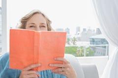 Blondynki kobiety obsiadanie na jej leżanki nakrycia twarzy z pomarańcze książką Zdjęcia Stock