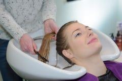 Blondynki kobiety płuczkowy włosy w salonie Fotografia Stock