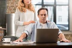 Blondynki kobiety pozycja za wzburzonym mężem używa laptop w domu Zdjęcia Stock