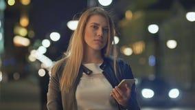 Blondynki kobiety use telefon komórkowy w mieście przy nocą zbiory wideo
