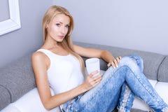 Blondynki młoda kobieta relaksuje w domu Zdjęcia Stock