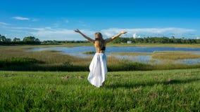Blondynki młoda kobieta stoi backwards w pięknym pole krajobrazie outdoors z podwyżek ręk rękami niebo zdjęcia stock