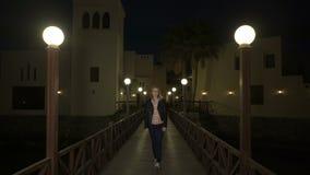 Blondynki młoda kobieta w skórzanej kurtce chodzi samotnie na drewnianym zwyczajnym moscie między latarnią przy nocą lub wieczór  zbiory